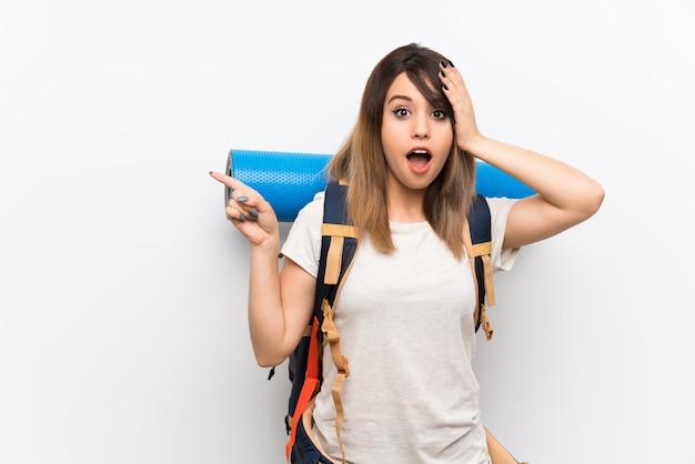 Mujer joven viajero sobre blanco sorprendido y apuntando el dedo hacia el lado