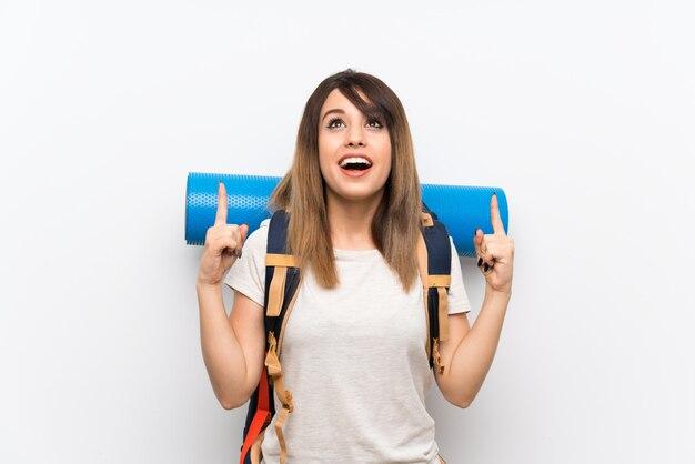 Mujer joven viajero sobre pared blanca apuntando hacia una gran idea
