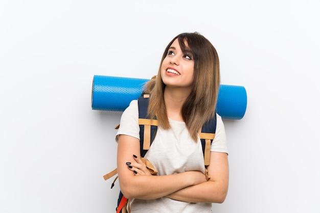 Mujer joven viajero sobre pared blanca mirando hacia arriba mientras sonríe