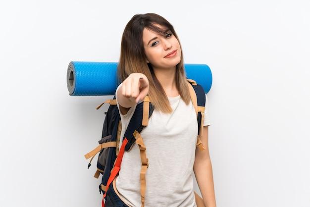 La mujer joven del viajero sobre la pared blanca te señala con una expresión segura
