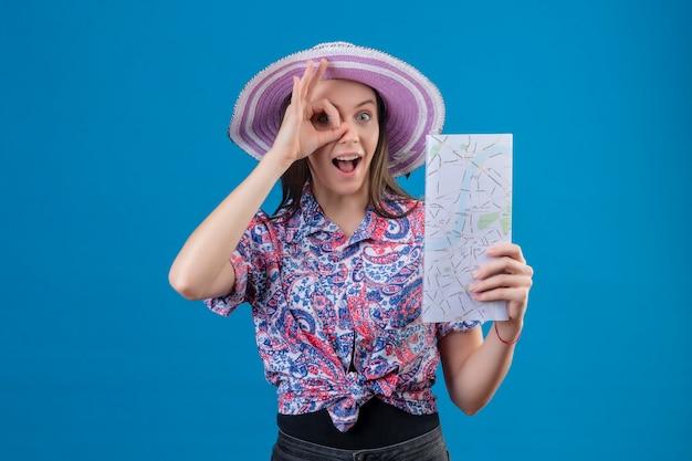 Mujer joven viajero con sombrero de verano sosteniendo mapa positivo y feliz haciendo bien firmar mirando a través de este cartel de pie sobre fondo azul.