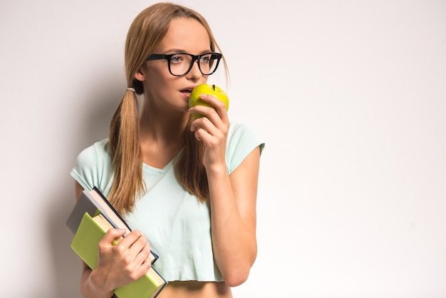 La mujer joven en vidrios está sosteniendo libros y una manzana.