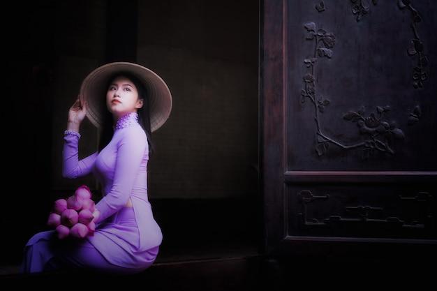 Mujer joven de vietnam que lleva la cultura ao dai tradicional en el antiguo templo de ho chi minh en vie