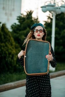 Mujer joven en vintage vestido de lunares negros con maleta retro en la mano posando afuera