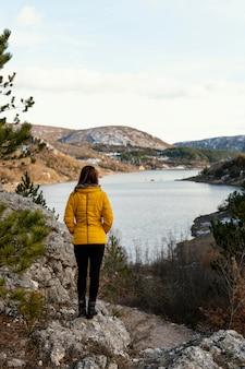 Mujer joven de visión trasera en la naturaleza