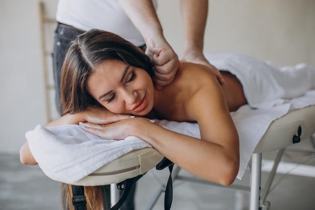 Mujer joven visitando masajista en el centro de spa