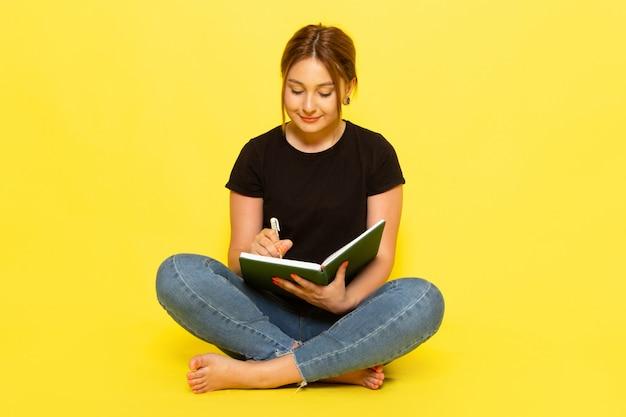 Una mujer joven de vista frontal sentada en camisa negra y jeans escribiendo notas con una sonrisa en su rostro en amarillo