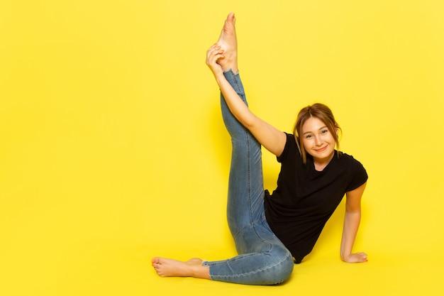 Una mujer joven de vista frontal sentada en camisa negra y jeans meditando y haciendo gimnasia en amarillo
