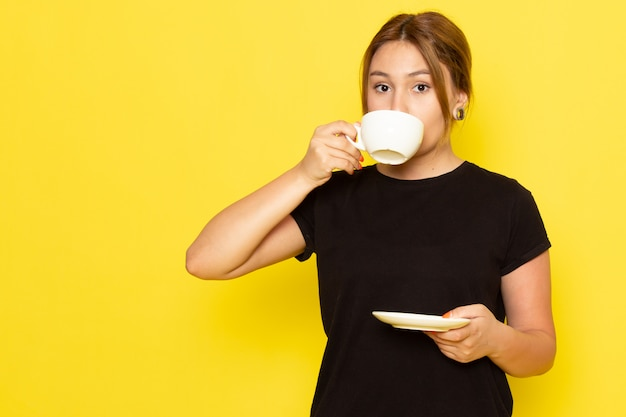 Una mujer joven de vista frontal en vestido negro tomando café en amarillo