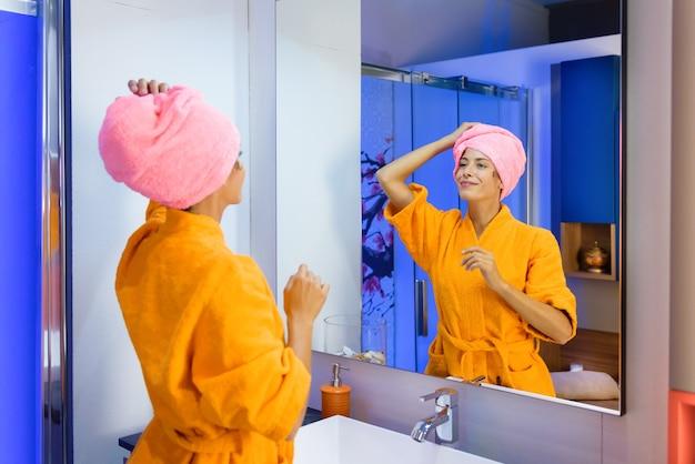 Mujer joven vistiendo una bata de baño naranja de colores brillantes con el pelo en una toalla después de la ducha mirándose en el espejo del baño