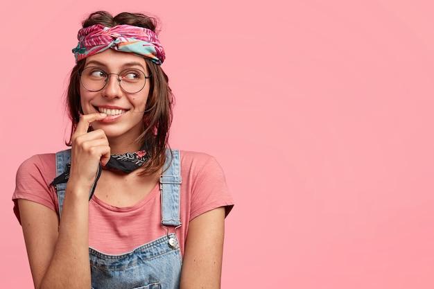 Mujer joven vistiendo coloridos overoles de mezclilla y diadema