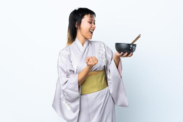 Mujer joven vistiendo kimono sosteniendo un tazón de fideos sobre blanco aislado celebrando una victoria
