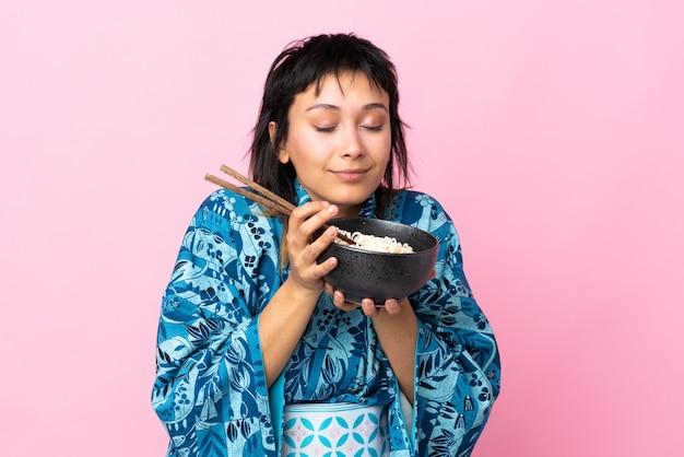 Mujer joven vistiendo kimono sosteniendo un tazón de fideos sobre blanco aislado