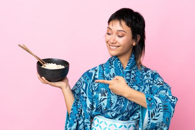 Mujer joven vistiendo kimono sosteniendo un tazón de fideos sobre espacio en blanco aislado