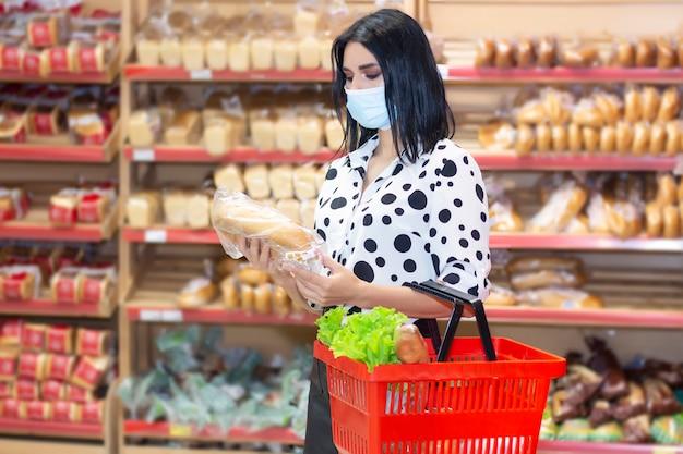 Mujer joven vistiendo máscara médica desechable de compras en el supermercado