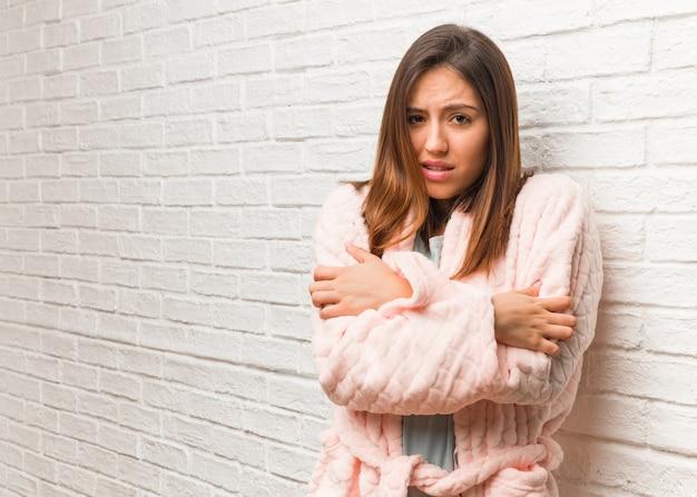 Mujer joven vistiendo pijama va frío debido a la baja temperatura