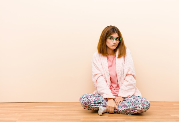 Mujer joven vistiendo pijama sentado en casa sintiéndose confundido y dudoso