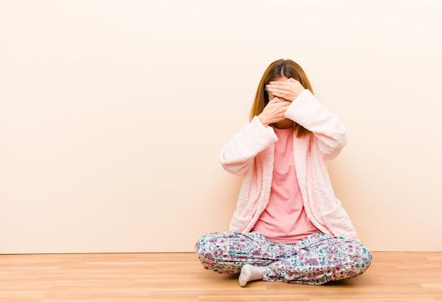 Mujer joven vistiendo pijamas sentado en casa cubriéndose la cara con ambas manos