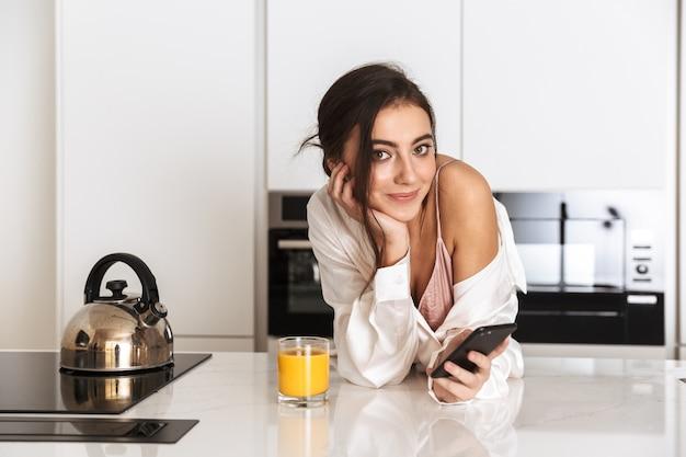 Mujer joven vistiendo ropa de seda bebiendo jugo en la cocina y usando un teléfono celular negro con una sonrisa