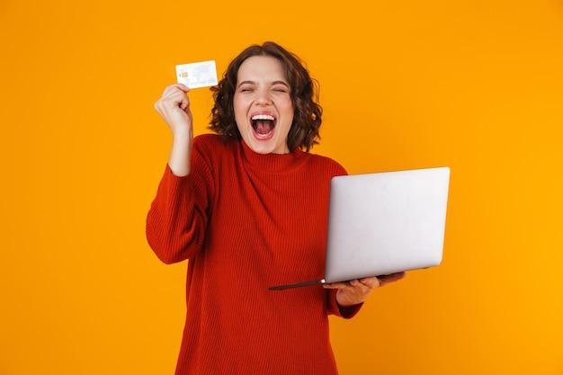 Mujer joven vistiendo un suéter usando una computadora portátil plateada y una tarjeta de crédito mientras está de pie aislado en amarillo