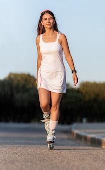 Mujer joven vistiendo un vestido de patinaje con patines en línea en una calle