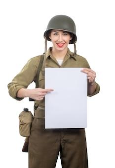 La mujer joven se vistió en los militares de wwii nosotros uniforme con el casco que muestra el letrero en blanco vacío con un copyspace