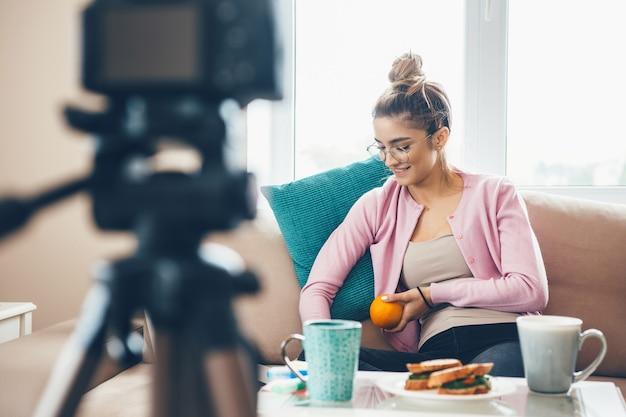 Mujer joven vlogging con una taza de té y sándwiches en la mesa mientras usa anteojos y sostiene una naranja