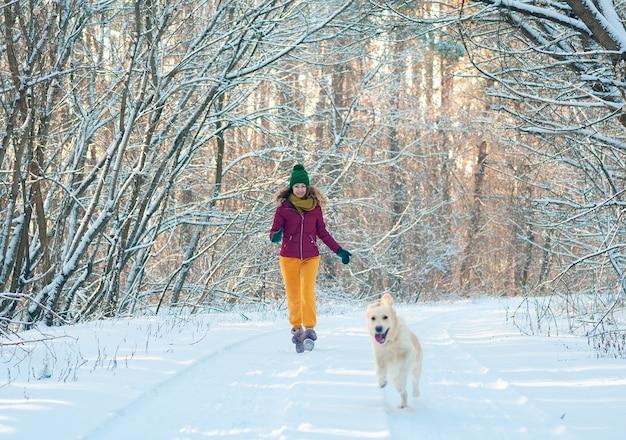 Mujer joven en winter park caminando con su perro