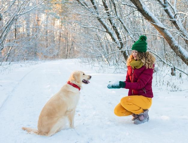 Mujer joven en winter park jugando con su perro