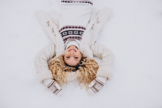 Mujer joven, yacer nieve, en el estacionamiento