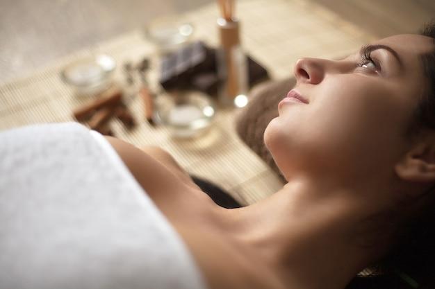 Mujer joven yacía en la cama de spa con ingredientes y materiales de spa