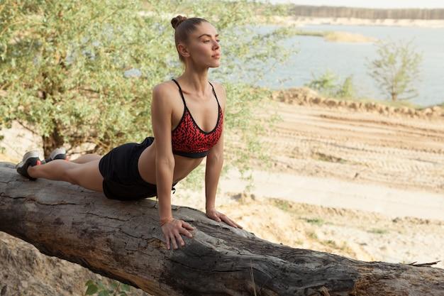 Mujer joven en yoga practicante superior del deporte rojo en naturaleza hermosa.