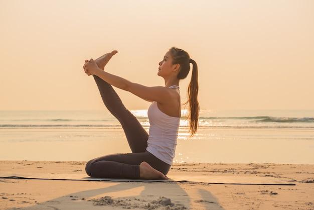 Mujer joven de la yoga que estira la pierna en la playa