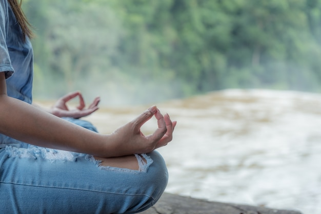 Mujer joven de la yoga que hace la meditación en la cascada.