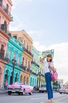 Mujer joven en zona popular en la habana vieja, cuba. hermosa chica viajera, coloridas casas en la ciudad