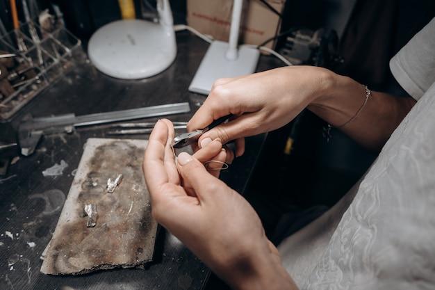 Mujer joyero corta un trozo de soldadura con pinzas