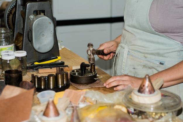 Mujer joyero trabajando en taller de joyería profesional en su mesa de trabajo.