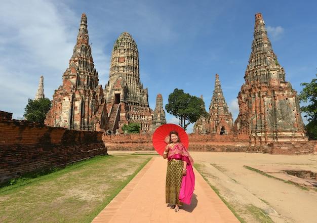 La mujer jubilada feliz en el vestido tailandés tradicional viaja en el templo.