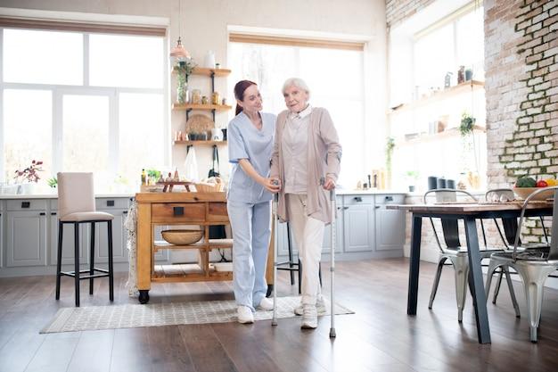 Mujer jubilada que se siente emocionada mientras camina con muletas