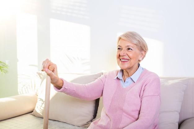 Mujer jubilada con su bastón de madera en casa. mujer mayor feliz que se relaja en casa sosteniendo el bastón y mirando a la cámara.