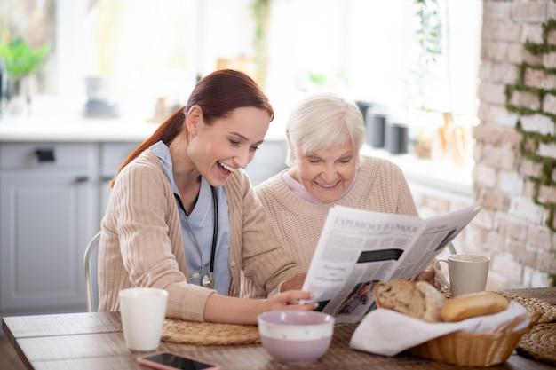 Mujer jubilada y su servicial cuidador riendo mientras leía el periódico