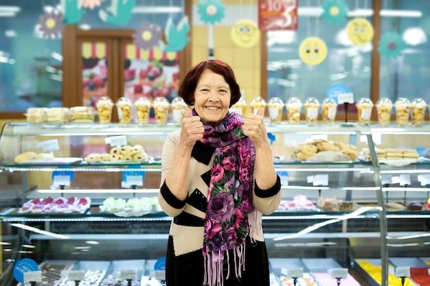 Mujer jubilada en una tienda de comestibles en el departamento de pan