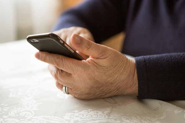 Mujer jubilada está utilizando el teléfono móvil, en la acogedora cocina de casa. la abuela tiene pausa para el café en la cocina
