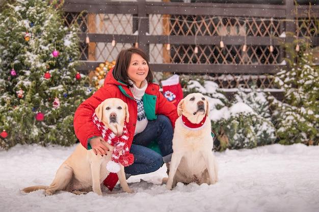 Una mujer juega con perros labradorsmi cerca de un árbol de navidad decorado durante una nevada en invierno en el patio de un edificio de apartamentos.