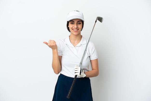 Mujer de jugador de golfista joven guapo aislada sobre fondo blanco apuntando hacia el lado para presentar un producto