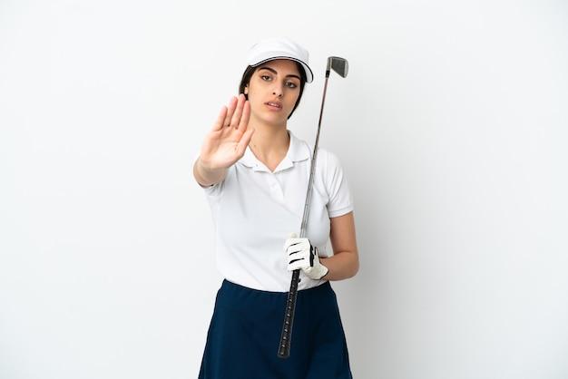 Mujer de jugador de golfista joven guapo aislada sobre fondo blanco haciendo gesto de parada