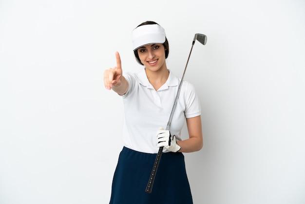 Mujer de jugador de golfista joven guapo aislada sobre fondo blanco mostrando y levantando un dedo