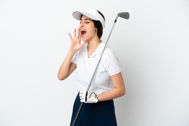 Mujer de jugador de golfista joven guapo aislado en la pared blanca gritando con la boca abierta hacia el lado