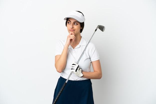 Mujer de jugador de golfista joven guapo aislado sobre fondo blanco con dudas y pensamiento