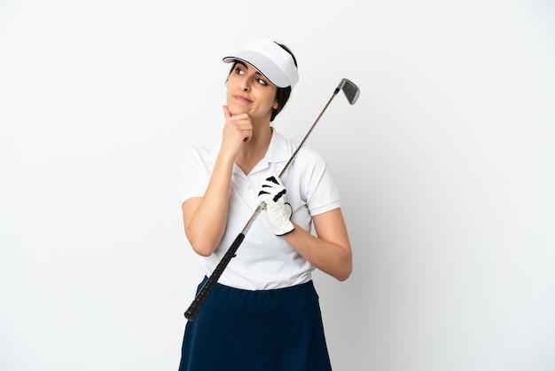 Mujer de jugador de golfista joven guapo aislado sobre fondo blanco con dudas